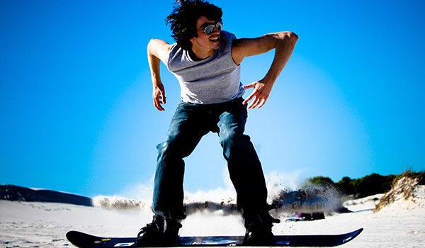 Young guy sandboarding
