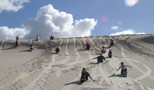 kids sandboarding on dunes